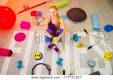 Girl blonde with fitness accessories top view. Inscription fitness