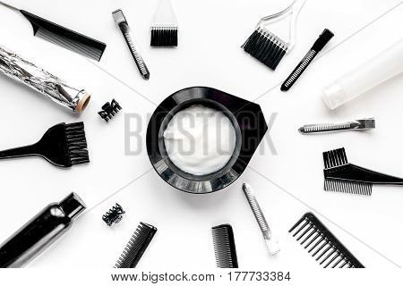 hairdresser working desk with tools for dye hair on white table background top view