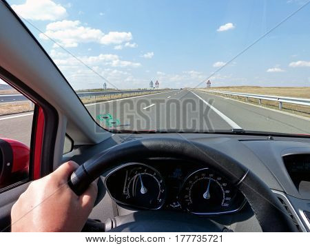 Fast driving on a straight highway on a sunny day