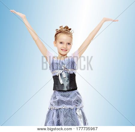 Slender little girl , with beautiful hair on his head, elegant long Princess dress.The girl raised her hands up and to the side.On the pale blue background.