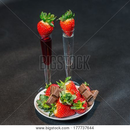 Liqueur And Vodka In Glasses With Strawberries, Strawberries With Pieces Of Chocolate On A White Sau