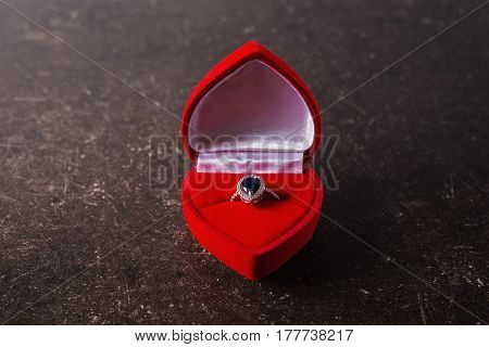 Red box with a silver ring with a black stone on a dark marble background. Ring in box concept. Silver ring with black stone