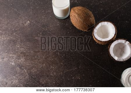 Coconut and coconut milk and oil on a dark marble background. Exotic large walnut. Personal care. Spa treatments