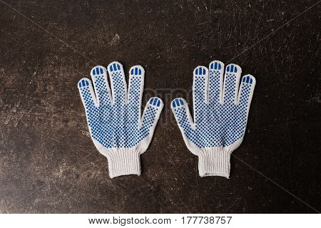 A pair of gloves. Working gloves on a dark marble background. Tidy up the house. Do makeovers. Gloves concept. Flat lay gloves