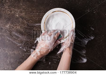 Wash dish concept. White dish detergent and sponge for dishes on a dark marble background. Hygiene. Wash dishes with gloves. Foam on the dishes