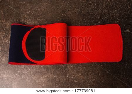 Belt for weight loss on a dark marble background. Relieve weight. Belt concept