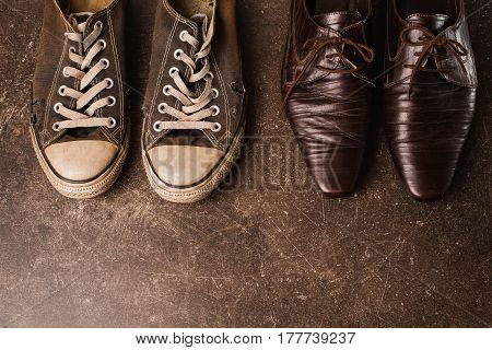 Footwear concept. Old black sneakers and brown classic shoes on a dark marble background. Footwear for outdoor activities. Classic footwear