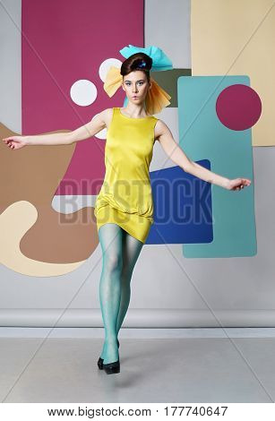 The eccentric girl is dancing on the background color.  Danish design. She dressed in a short yellow dress, green pantyhose, high heels. View from the back. Back background: circles, chair for eggs.