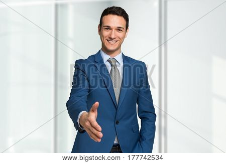 Smiling young businessman giving an handshake
