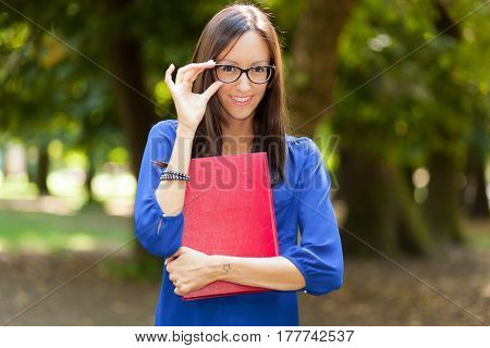 Beautiful girl holding a book at the park