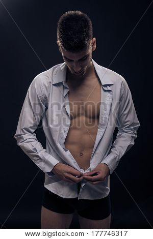 One Young Man Buttoning Shirt