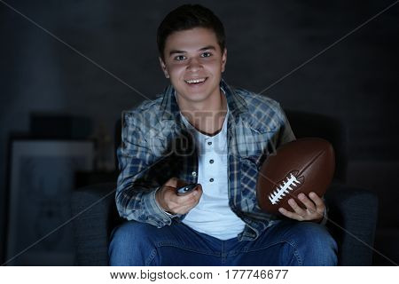 Teenager watching rugby late in evening