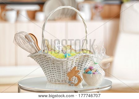 Easter basket with gifts and painted eggs on light blurred background