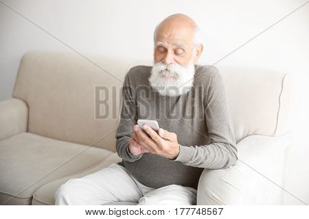 Senior man sitting on sofa with smart phone in room