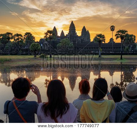 Asian Tourists Taking Picture Of Angkor Wat At Sunrise