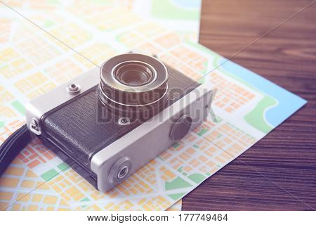 Vintage camera with map on wooden background