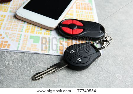 Car key, phone and map on grey table