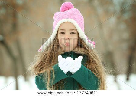 Pretty little girl sending air kiss outdoors in winter