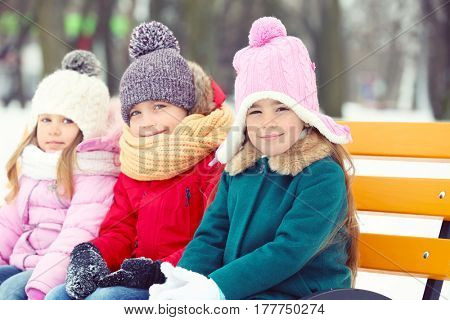 Happy children sitting on wooden bench outdoors in winter