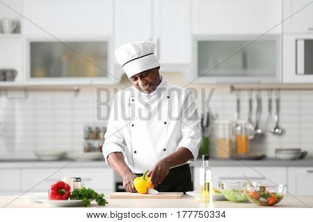 Mature Indian chef cooking in kitchen