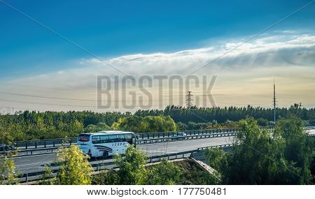 Beijing, China - Oct 31, 2016: Traffic running along the countryside highway soon after leaving Beijing city. Captured from within a High-Speed Rail (HSR) bullet train traveling at 300 km/h.