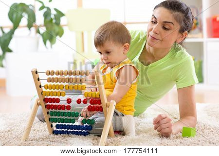 kid and mother playing with abacus at home interior