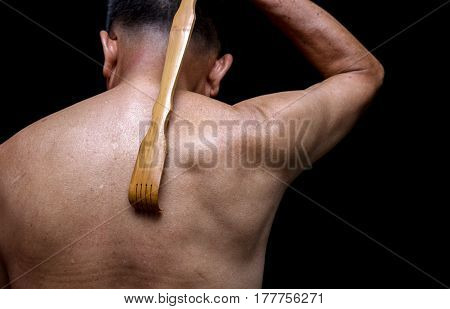 close up of back scratching oldman with his long handle bamboo stick back scratcher.