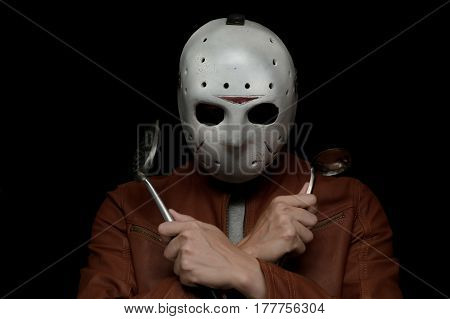 creative chef holding his ..... and .... with a ice hockey mask in isolated black background