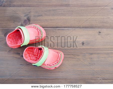 Top view of colorful Children's rubber sandals on wooden background