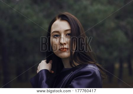 Girl with dark hair in the forest. She wears a black leather jacket. Portrait of a smiling girl with freckles.