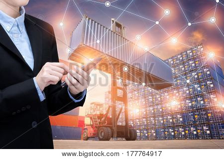 Smart Business woman use smartphone and internet of things technology for Global business connection with global customer for worldwide container cargo shipping.Logistic Import Export business concept