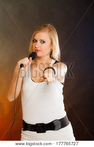 Karaoke music singer concept. Portrait of blonde woman singing to microphone young star performing having fun studio shot.