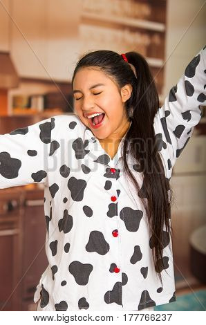 Young brunette woman posing in pyjamas, interacting with camera by stretching and yawning.