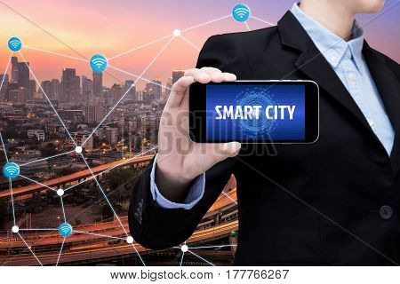 Young Smart business woman is using smart technology of internet of things in smart city for global business connection. Photo design for smart city and smart technology internet of things concept