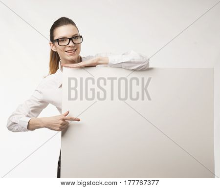 Young happy woman portrait of a confident businesswoman showing presentation, pointing on paper placard over gray background. Ideal for banners, registration forms, presentation, landings, presenting concept.
