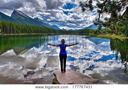 Young woman embracing the lake with reflections of clouds and mountains. Honeymoon lake. Banff National Park. Canadian Rockies. Alberta. Canada.