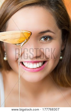 Young brunette woman sitting holding wooden knife with golden honey dripping from it, smiling happily.