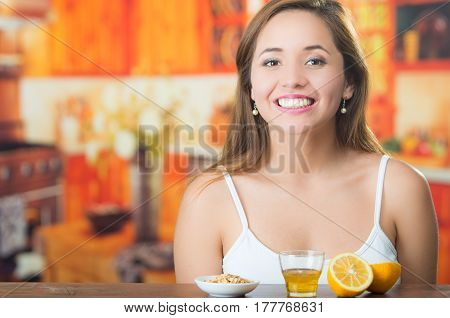 Young brunette sitting by table with glass of honey, granola and sliced lemon in front, smiling happily.
