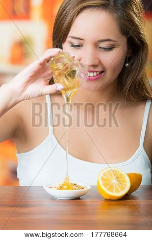 Young brunette woman sitting while pouring honey into small plate from glass and smiling.