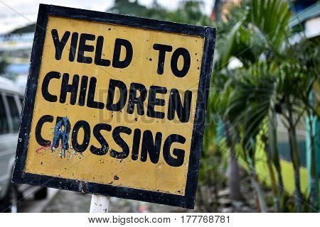 A hand made wonky 'Yield to Children' sign in yellow and black.