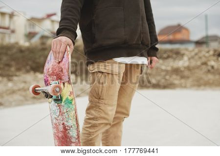 teenager standing in a black hoodie holding a hand skateboard on the background slum
