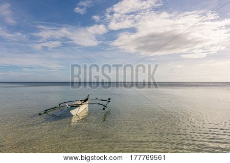 A Filipino fisherman's basic pump boat floating empty on a still calm tropical sea with seagulls resting on its stabilizers.