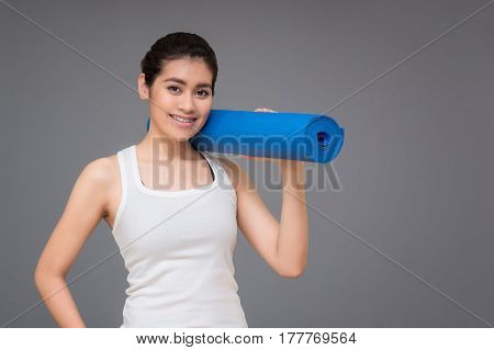 Young asian woman with happy smile holding her yoga mat at yoga healthy sport gym. Yoga and meditation have good benefits for health. Photo concept for Yoga Sport and Healthy lifestyle.