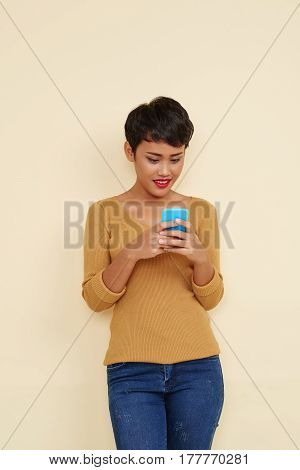 Portrait of young cheerful Filipino woman text messaging