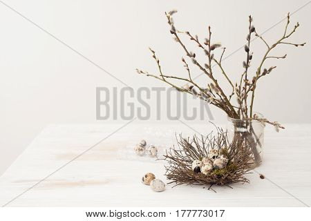 Quail Eggs In The Nest Of Willow Branches In A Glass Jar On A Wooden White Table