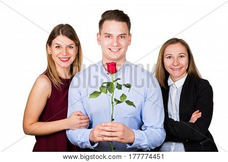 Picture of a young man holding a red rose posing with two beautiful woman bigamy