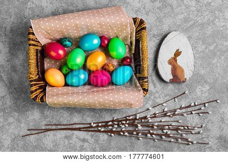Easter card. Painted eggs of chicken and quail in a basket. Sprigs of the Easter willow. Wooden egg with an Easter bunny. Gray concrete background. Top view from above copy space.