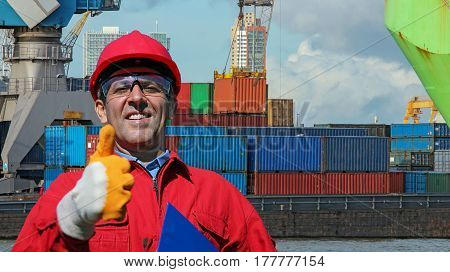 Worker Gesturing Thumb Up Near Container Terminal.  Worker supervising container uploading at dock.