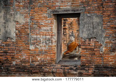 The old Buddha statue, look through the window in the ancient country of Thailand.