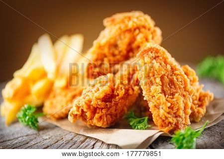 Fried chicken wings on wooden table. Breaded Crispy fried kentucky chicken tasty dinner.